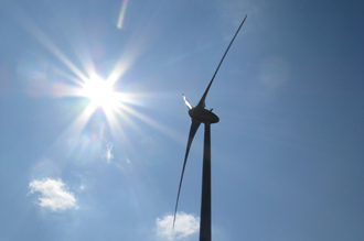 Three-wing wind turbine in front of the sun with a blue sky